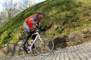 Lance climbing a muir at the 2010 Tour of Flanders