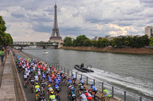 the peleton rides down the banks of the Seine on their way to the final straight over the Champs d'Elysee